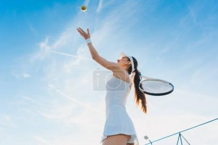 Woman playing tennis giving service