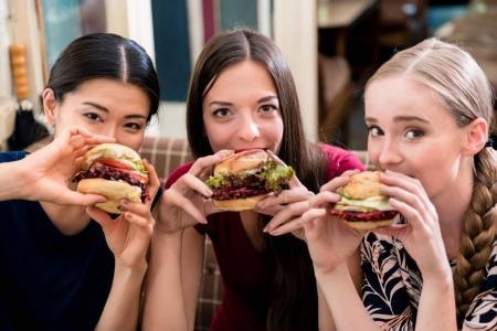 Portrait of three young women eating hamburgers