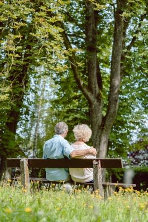 Romantic elderly couple sitting together on a bench in a tranqui