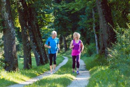 Photo pour Vue de face de toute la longueur de deux aînés avec un mode de vie sain souriant en faisant du jogging ensemble à l'extérieur dans le parc - image libre de droit