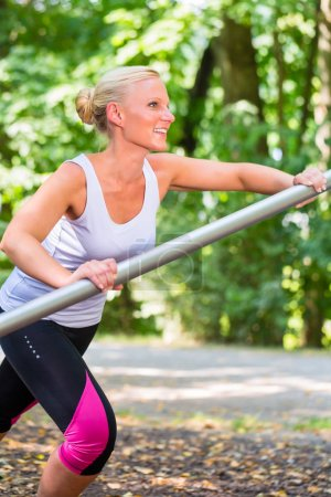 Young woman stretching before sport on fitness trail