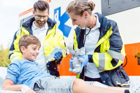 Emergency medic giving soft toy to console injured boy