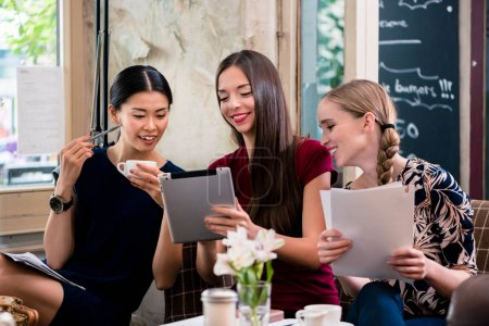 Young women holding files in a coffee shop