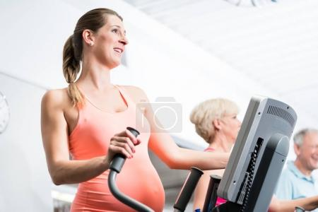 Pregnant woman training on cross trainer at the gym