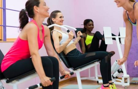 Woman in gym using modern equipment for toned arms during interv