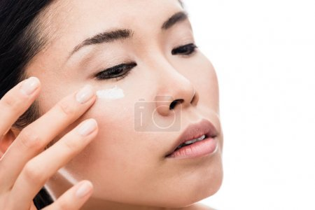 Young woman applying anti-wrinkles eye moisturizer