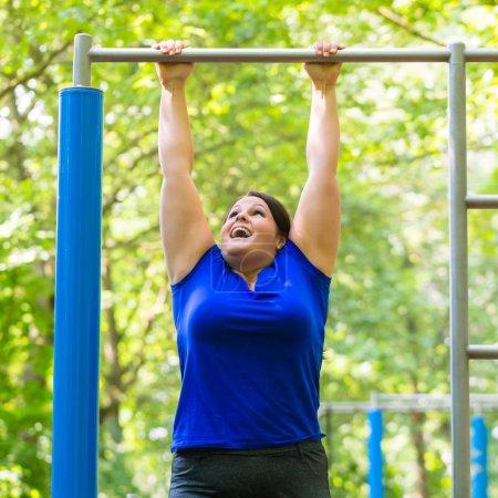 plump woman making sport exercises at high bar