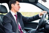 Man driving in his car in business attire
