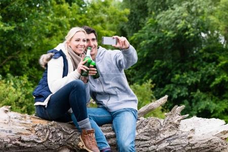 Woman and man drinking beer taking selfie while hiking