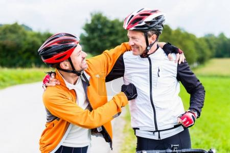 Bicyclists embrace each other in finish celebrating