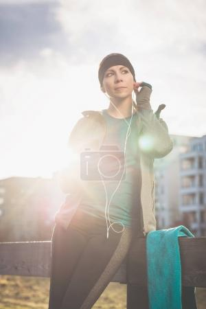 Young woman ready for outdoor workout listening to music through