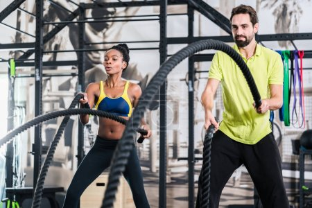 Functional training with battle rope in crossfit gym