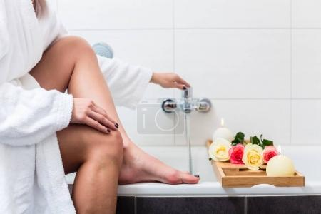 Woman preparing wellness bath in tub.