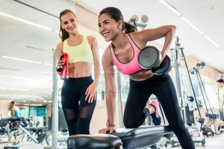 Powerful young woman smiling while rowing with one arm in a tren