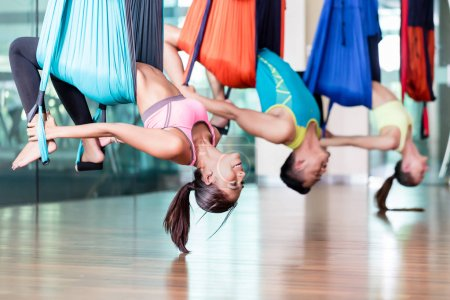 Fit young woman practicing aerial yoga during group class in a m