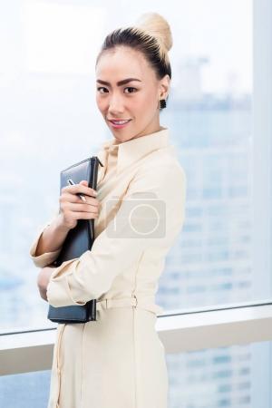 Photo pour Femme d'affaires asiatique devant la fenêtre du gratte-ciel dans le bureau - image libre de droit