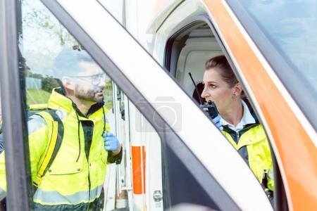 Paramedics in ambulance in radio contact with headquarters