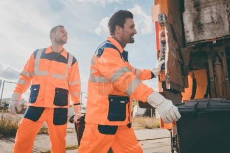 Two garbagemen working together on emptying dustbins