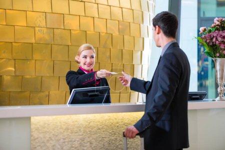 Photo pour L'homme à l'hôtel s'enregistre à la réception ou à la réception reçoit une carte-clé - image libre de droit