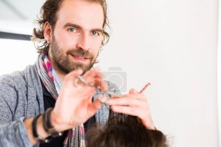 Barber cutting man hair in haircutter shop