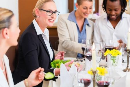 Group of man and women at business lunch in restaurant eating and drinking