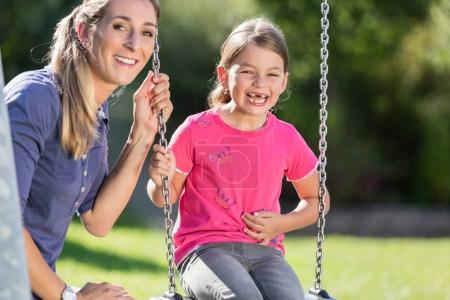Woman with laughing girl on swing having fun together