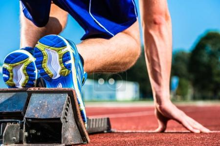 Photo for Runner before start signal on starting block of sprint track in sport stadium - Royalty Free Image