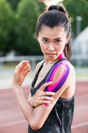 Woman taping with therapeutic tape on cinder track of sports sta