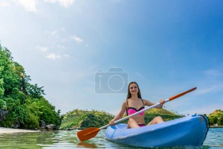 Young woman paddling during vacation in an idyllic travel destin