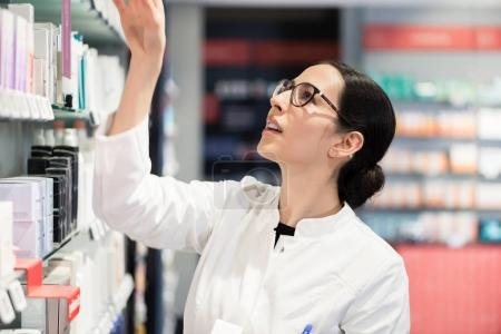 Pharmacist standing in front of various products