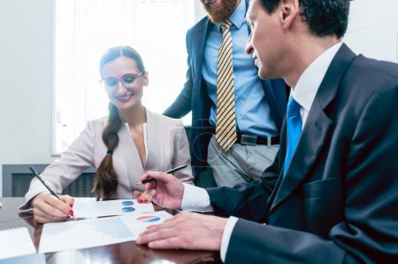 Photo for Business analyst smiling while interpreting financial reports showing profit and development during meeting with his female colleagues in the office - Royalty Free Image