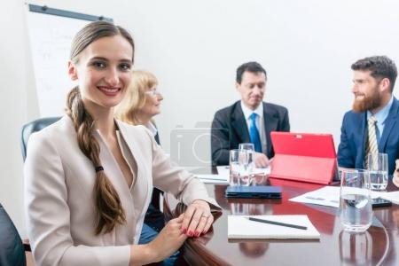 Portrait of a beautiful business woman looking at camera during meeting
