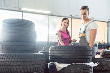 Photo for Handsome auto mechanic helping a female customer to choose from various high-quality tires in a contemporary automobile repair shop - Royalty Free Image