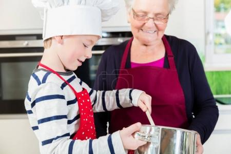 Granny and little boy preparing food in kitchen