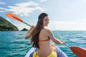 Young woman paddling a canoe on the sea during summer vacation