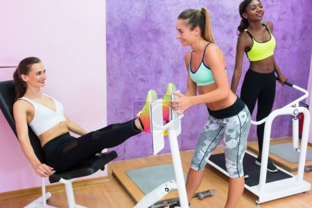 Determined fit women exercising under guidance of experienced fitness instructor