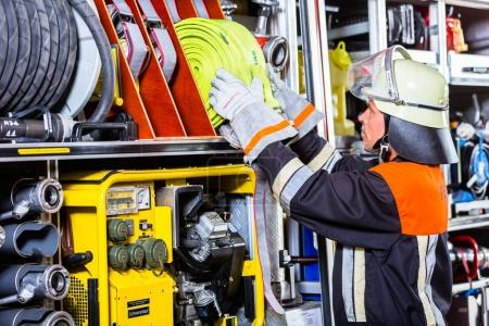 Fire fighters loading hoses into operations vehicle