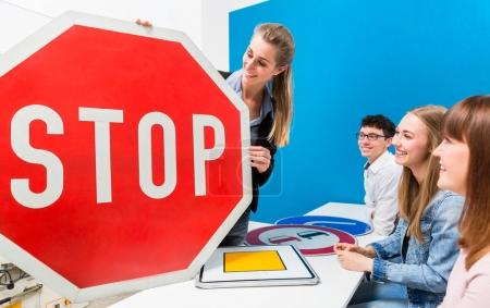 Driving teacher explaining meaning of street signs to class