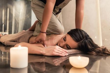 woman enjoying the healing benefits of traditional Thai massage at luxury spa and wellness center