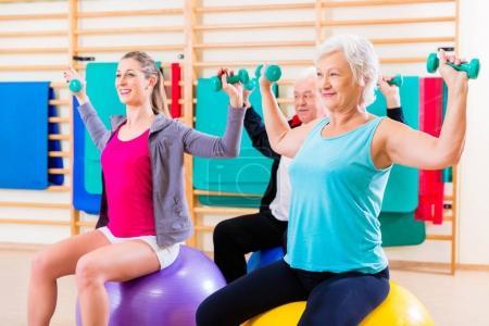 Photo pour Groupe de seniors et jeunes gens à faire des exercices de physiothérapie - image libre de droit