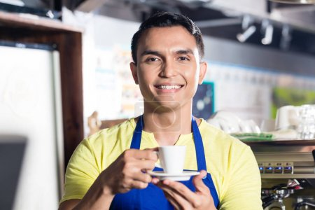 Barista in Indian cafe holding cup