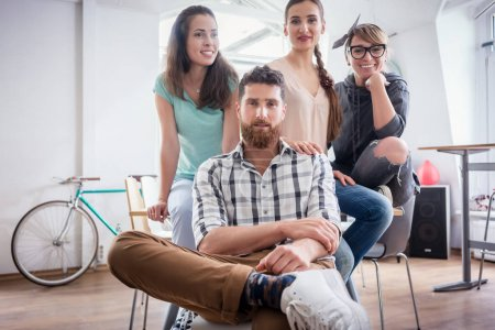four co-workers wearing casual clothes during work in a modern hub