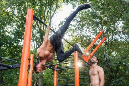 Shirtless bodybuilder hanging on horizontal bar during workout