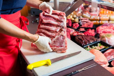 Butcher woman cutting piece of rib meat in her shop