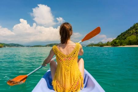 Young woman paddling a canoe during vacation in Flores Island, Indonesia