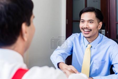 Subordinate professional talks to supervisor in office building