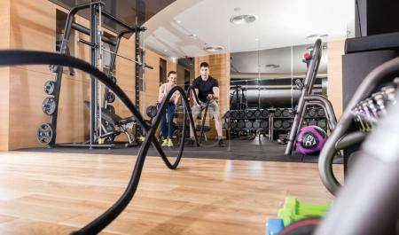 Young determined man waving battle ropes with alternative motion