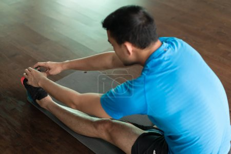 Man sitting down on exercise mat while touching his toes