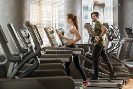 Photo for Side view of fit young man and woman smiling while running side by side on modern electric treadmills at the gym - Royalty Free Image