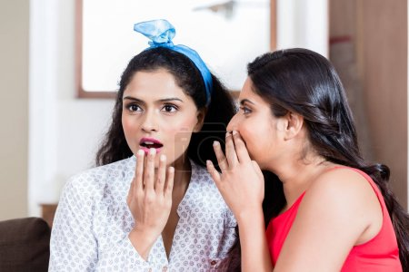 Young woman whispering to her best friend gossips